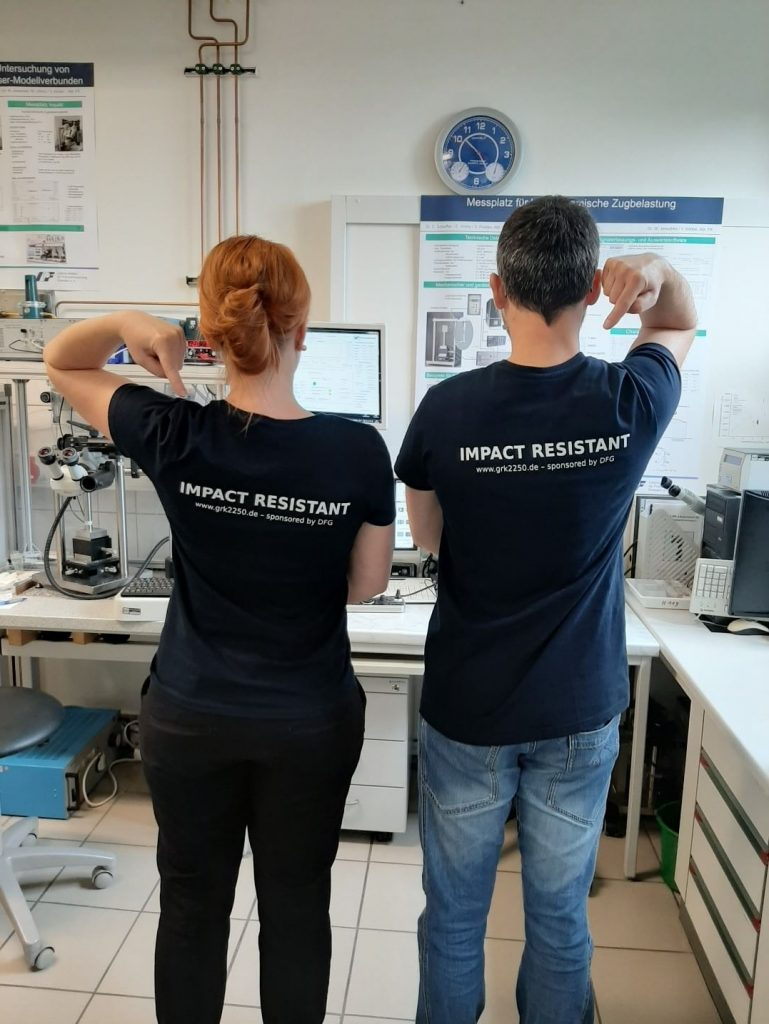 """Participants of the laboratory sessions wearing GRK 2250 corporate T-shirts with the slogan """"Impact Resistant"""""""